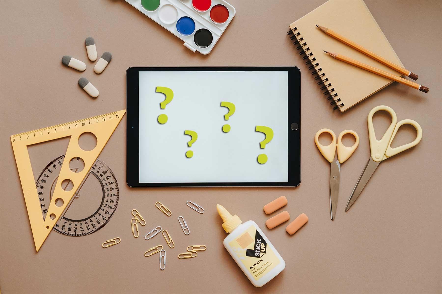 Schreibtisch mit Tablet und verschiedenen Zeichen- und Mal-Werkzeugen - Symbolische Darstellung für den Fragenkatalog für Website-Angebote